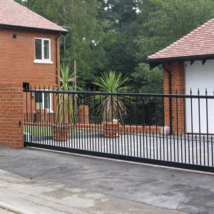 Large wrought iron driveway gate with sliding automation